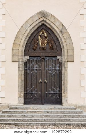 Old wooden oak arched gothic church doorway with black wrought iron hinges. Large wooden door with wrought-iron elements. Decorative door with fittings.