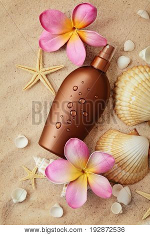suntan lotion and seashells on the sand beach