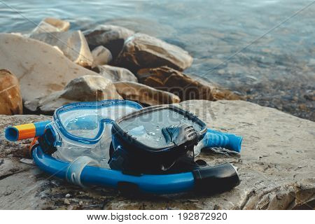 Two Masks For Diving And Tubes Lie On The Beach On The Rocks. Tourism And Travel Concept