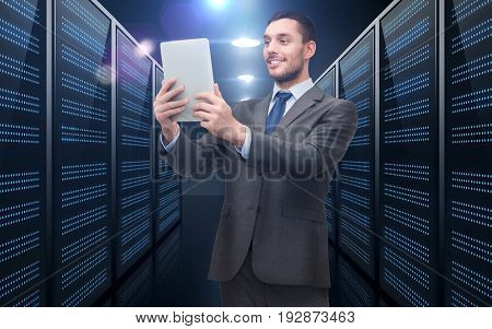 business, people and technology concept - happy smiling businessman in suit holding tablet pc computer over futuristic server room background