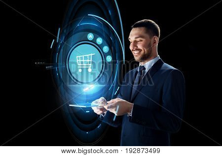 business, e-commerce and modern technology concept - smiling businessman in suit working with transparent tablet pc computer and virtual shopping cart projection over black background