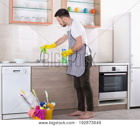 Man Cleaning Kitchen Faucet
