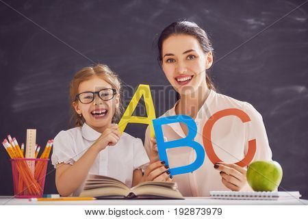 Back to school! Child is learning to write. Adult woman teaches child the alphabet.