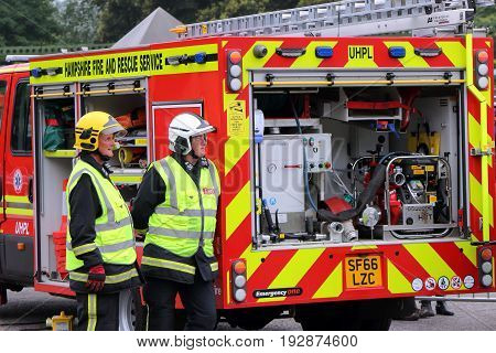 Beaulieu, Hampshire, Uk - May 29 2017: Two British Firemen Or Firefighters Standing At The Rear Of A