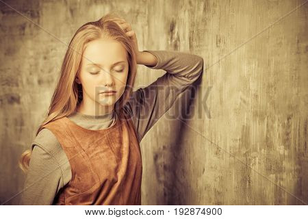Portrait of a cute blonde girl teenager standing with closed eyes by a grunge wall. Sepia.