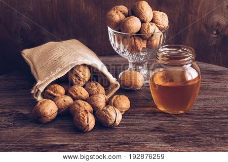 Nuts with honey on the table. Walnuts in a canvas pouch. Still life with nuts and honey.