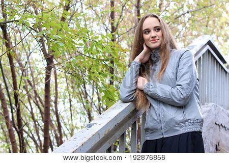 Beautiful young girl in leather jacket standing and posing in autumn park. Pretty young woman with long straight brown hair