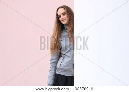 Fashion girl with long hair wearing black skirt, trench coat and gray leather jacket, posing against wall, street style, autumn outfit