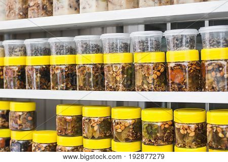 Glass jars with nuts and honey on counter in a market
