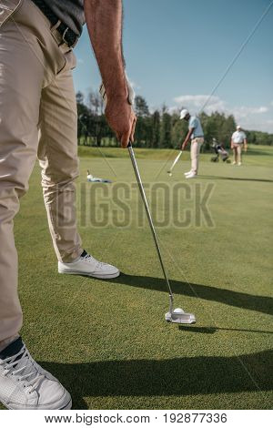 cropped shot of golfer getting ready to hit a ball on golf course at daytime