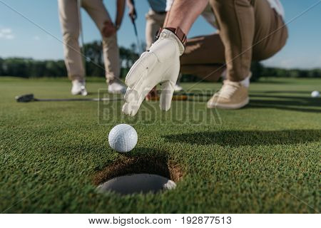 cropped shot of golf player in glove trying to get ball near the hole
