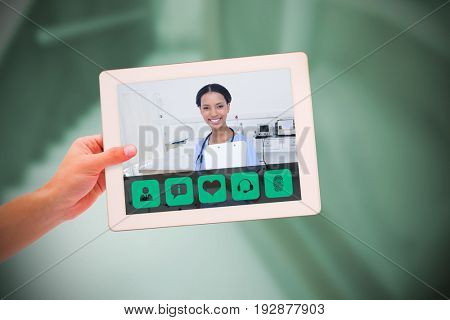 Masculine hand holding tablet against empty bed in the hospital room