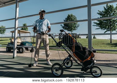 stylish golf player with golf club in hand standing near golf bag with equipment