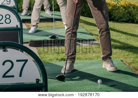 Cropped Shot Of Group Of Golf Players Playing Golf Together At Golf Course