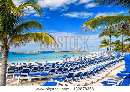 Great stirrup cay Bahamas - January 8 2016: rows of blue lounge chairs on sunny beach with white sand green palms people and cruise ship in blue sea on idyllic skyline. Summer vacation in paradise
