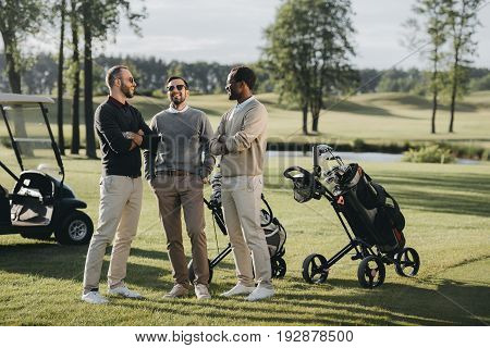 Multiethnic Golfers With Golf Clubs Talking And Spending Time Together On Golf Course