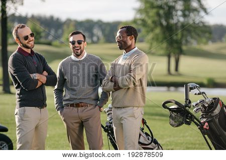 happy multiethnic golfers spending time together in golf course poster