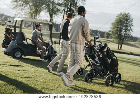 Multiethnic Golf Players With Golf Bags And Golf Cart Spending Time Together
