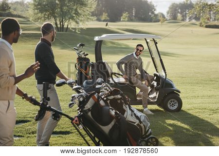 Multiethnic Friends With Golf Bags And Golf Cart Spending Time Together On Golf Course