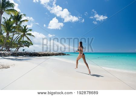Young pretty woman with beautiful body in swimsuit running in ocean water sunny day at tropical beach wellness concept