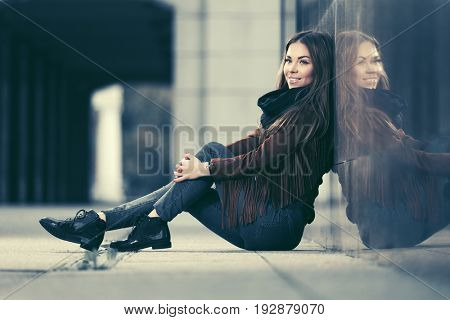Happy young woman sitting at the wall in city street. Stylish fashion model in leather fringe suede jacket and blue jeans