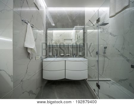 Modern bathroom with light tiled walls. There is a shower with a glass door, two white sinks with faucets, mirror over them, luminous lamps, hanger with a towel. Indoors. Horizontal.