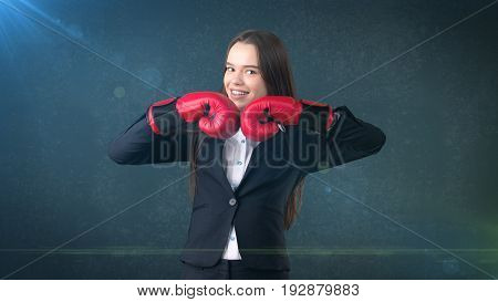 Young Beautiful Woman In Black Suit And White Shirt Standing In Combat Pose With Red Boxing Gloves.