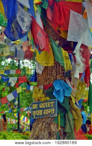 Be quiet - placard with a call for silence on Sacred Bodhi tree - a place of Buddha enlightenment.