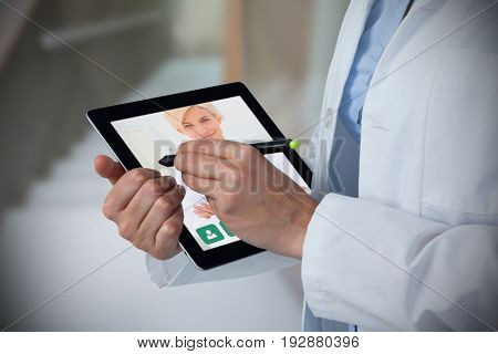 Midsection of female doctor using digital tablet with stylus against empty bed in the hospital room