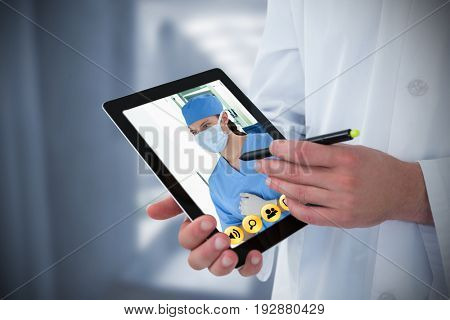 Doctor using digital tablet against wheelchair in the corridor