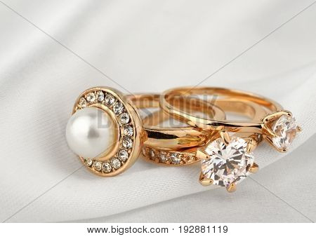 jewelry rings with diamonds and pearl on white cloth