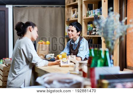 Profile view of female customer with ponytail reading label on honey jar while middle-aged shop assistant looking at her with warm smile