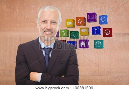Digital composite of Business man with arms cross with icons on the back