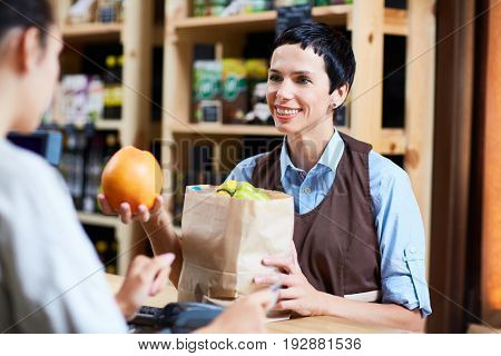 Waist-up portrait of friendly cashier putting fruits in paper bag while female customer paying for shopping