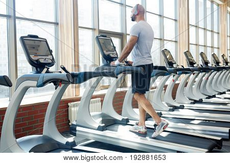 Back view portrait of muscular sportsman running on treadmill listening to music  alone in empty sunlit gym