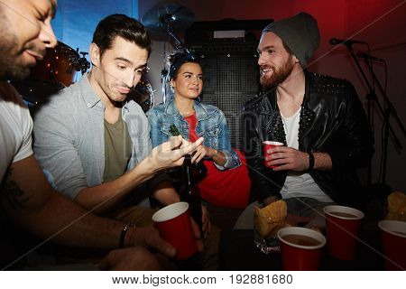 Group of modern young people chatting, drinking beer and having fun  at late night party