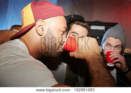 Group of trendy young men playing drinking games at party, having beer competition