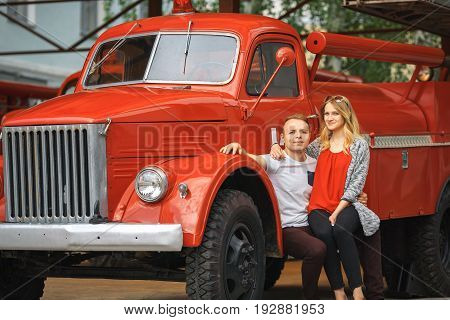 Vintage Firefighting Truck And A Couple In Love. Outdoor Portrait Of A Beautiful Young White Girl An