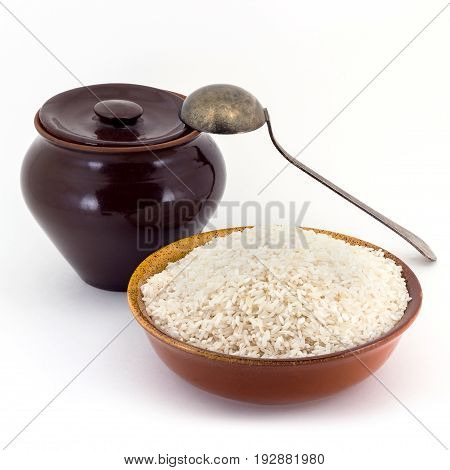 Still life of Rice cereal in ceramic pial, ceramic pot, old spoon isolated on white background