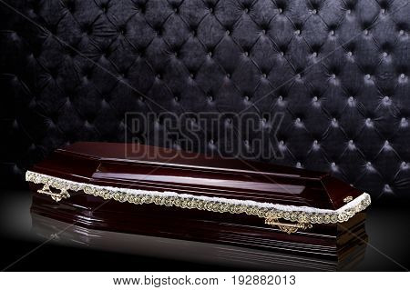 closed wooden dark brown coffin isolated on gray luxury background. casket, sarcophagus on royalbackground. Ritual objects for burial. Conduct of the deceased on his last journey. Surrender body dust of the earth. Christian funeral ritual