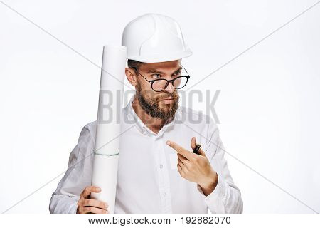 Engineer on a white isolated background, showing a finger on a blueprint, builder.