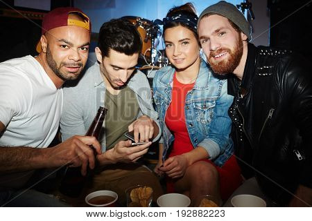Group of young people, men and woman,  looking at camera and posing in underground night club, having fun