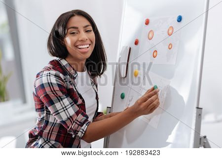 Visual presentation. Joyful happy young woman standing near the whiteboard and smiling while putting visual materials on it