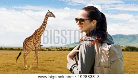 travel, tourism and people concept - happy young woman with backpack over african savannah and giraffe background