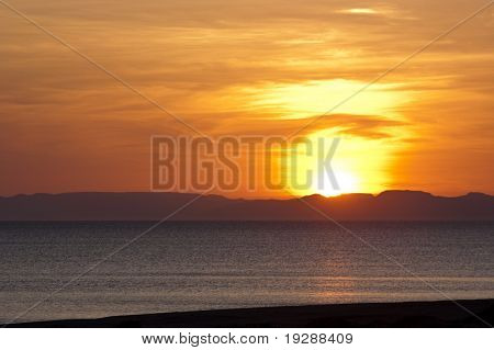 Pink and vibrant red sunset with sun behind mountainous horizon and ocean