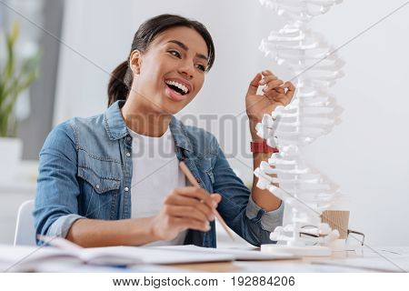 Genetic science. Positive female genetic scientist smiling and taking notes while looking at the DNA model
