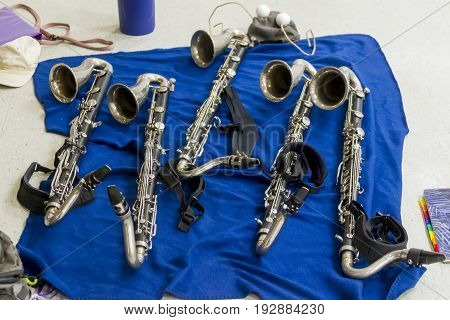 several bass clarinets resting on a blanket during rehearsal