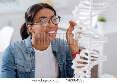 Future biologist. Smart nice young student sitting at the table and looking at the DNA model while studying biology