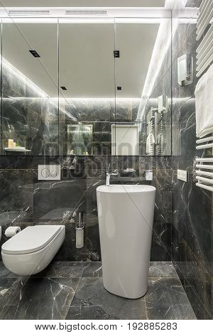 Modern restroom with textured dark tiled walls and luminous lamps. There is a white toilet, toilet paper dispenser and a brush, tall sink with a chrome faucet, hanging towel rack, large mirror.