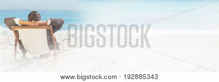 Young businessman relaxing on his sun lounger on the beach